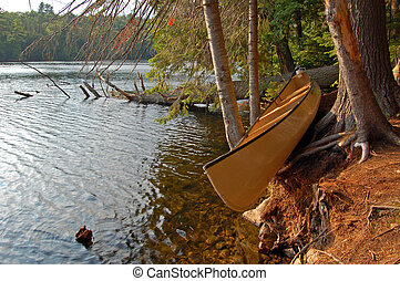 Canoe on shore - Sunny evening after day of canoeing in...