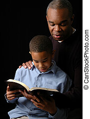 Father and Son - Father and son reading a Bible over a black...