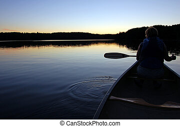 Canoeing - Sunset and canoe trip in calm lake in Algonquin...