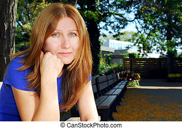 Sad woman - Mature woman looking sad and tired sitting on a...