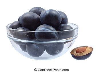 Glass bowl full of plums and one plum half, isolated on...