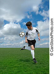 Soccer Player - Soccer player performing a back kick over a...