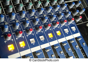 Audio Mixing Console - An array of rotary controls, sliders,...