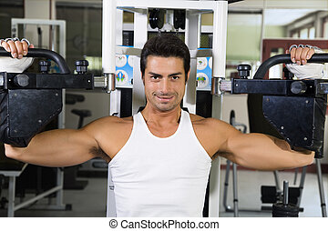 health club: guy in a gym doing weight lifting