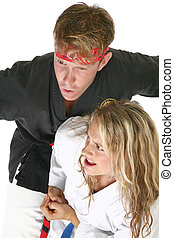 Woman in martial arts uniform elbows a man