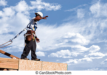Balancing Act - A construction worker walking across the top...