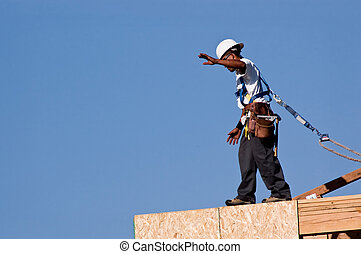 Wall Walker - A construction worker walking across the top...
