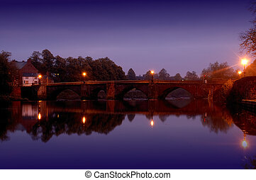 Stone Bridge at Night - Old stone arch bridge crossing the...