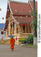 Buddhist Monk in Laos - A buddhist monk shields himself from...