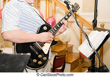 playing the guitar - a man playing on his black guitar