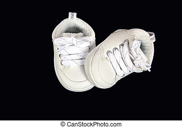 Infant tennis shoes - Two baby tennis shoes on a black...