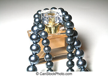 Luxuries - perfume wrapped in black pearls