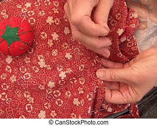 women sewing a hem - hands stitching a hem dress