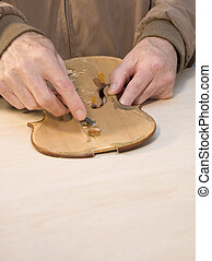 violin repair - luthiere scrapes hide glue off of an old...