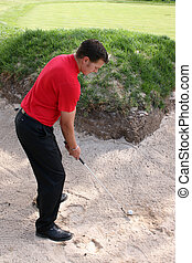 Preparing for bunker shot - Young golfer preparing for a...