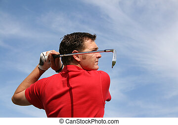 Iron Shot - Young golfer hitting an iron against a half...