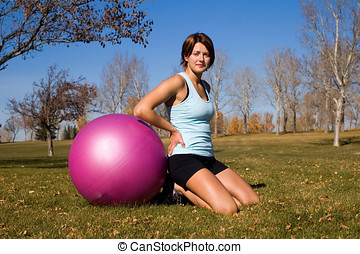 Exercise ball - Young woman in tanktop, beside purple...