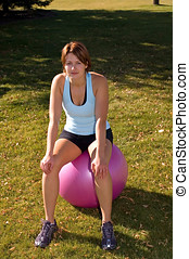 Exercise ball - Young woman in tanktop, sitting on exercise...