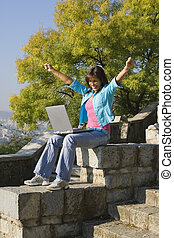 Computer excitment - Outdoor happy young woman getting good...