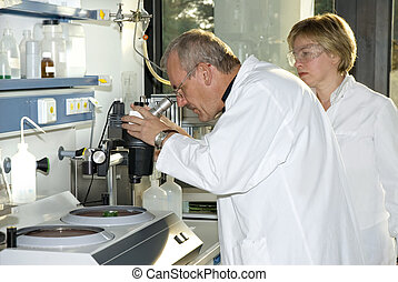 work in laboratory - Two science technicians at work in the...