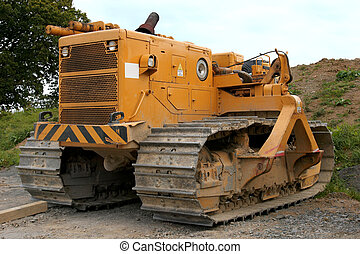 Bulldozer - Large yellow bulldozer standing idle on rough...