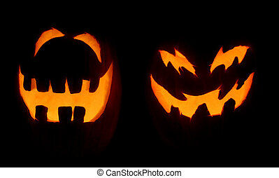 Two Scary Pumpkins - Two carved pumpkins glow on Halloween...
