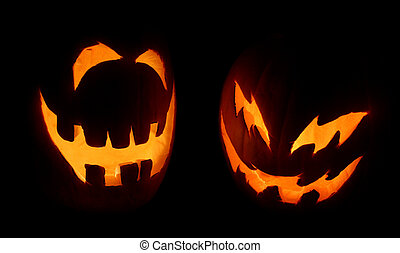 Two Jack-o-Lanterns - Two carved pumpkins glow on Halloween...