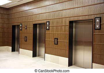 Modern elevators with metal doors wood panelling