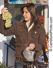 Vegtables market-grapes - Image of a young woman in a...