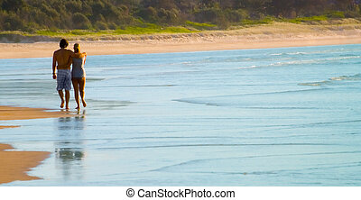 Loving Couple walk along Beach - attractive young couple in...