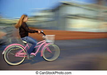 Girl on Pink Bike - An intentional slow-shutter blur, gives...