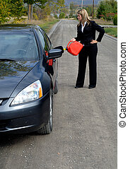 Car Breakdown - Businesswoman Filling Her Car Up With...