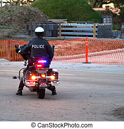 Police officer sitting on Motorcycle  - back view