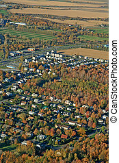 Aerial view of houses and fields in bright colors of autumn.