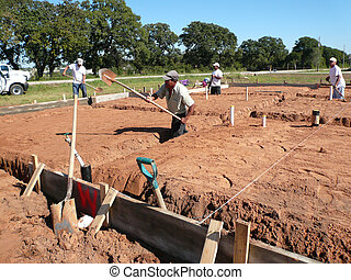 Laborer Digging - Construction Laborer digging a beam for a...