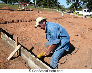 Laborer Drilling a hole in the form for the foundation