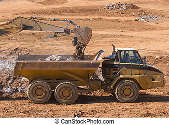 Dump Truck - A dump truck being loaded by a backhoe
