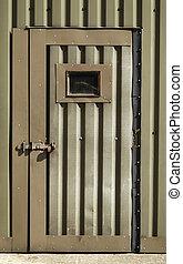 old wartime door - battered metal door of an old military...
