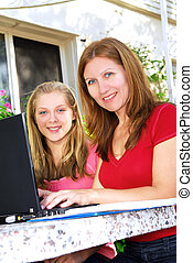 Mother and daughter with computer - Mother and daughter...