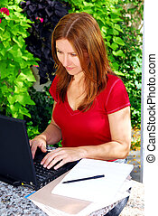Working at home - Mature woman working on portable computer...