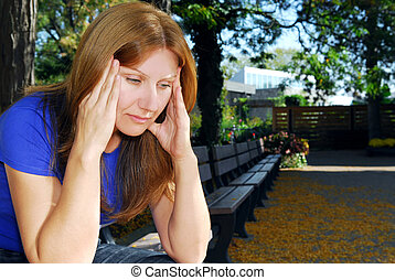 Woman with headache - Mature woman with a headache sitting...