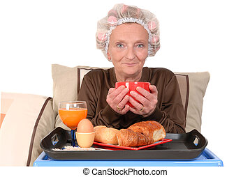 businesswoman in bed, breakfast - Middle aged businesswoman...