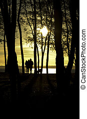 Family at sunset - A silhouette shot of a family walking in...