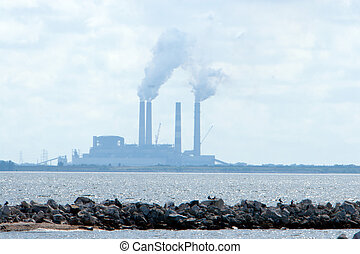 Air Pollution - Industrial or power plant shrouded in smoke,...