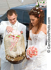 Happy couple - young couple in wedding wear with bouquet of...