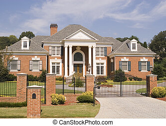 Brick House Iron Fence - A massive brick house behind a...