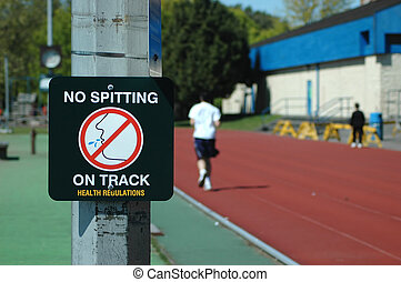 "No Spitting - A \""No spitting\\\"" sign with a man jogging..."