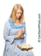 Praying girl with a bible on her lap, isolated on white...