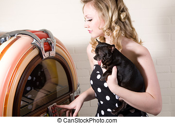 Picking a song - Pretty blond girl with chihuahua on her arm