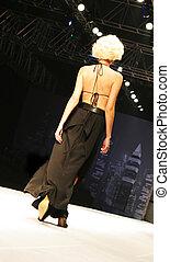 Model on the catwalk - Blond model in a sexy dress walks...